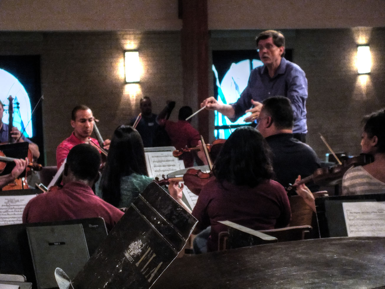 Leon Hauck works with the string section on the Adagio in G Minor, at Forest Lake Church on Oct. 5